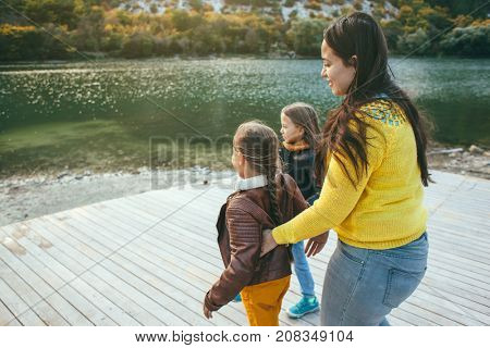 Family spending time together by the lake in autumn. Mom with her daughters playing near the pond. Fall weekend in the open air.