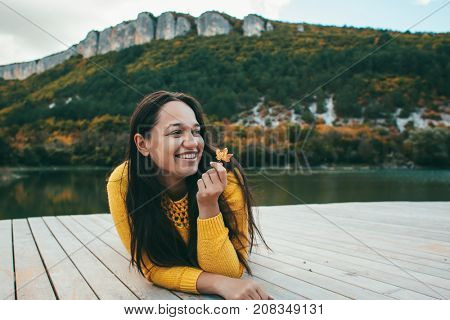 Young woman spending time by the lake in autumn. Plus size girl relaxing near the pond. Fall weekend in the open air.