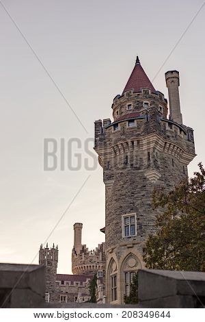 golden sun setting over tower detail of castle casa loma in Toronto red tiles roof old antique romantic