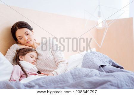 Support. Caring loving kind mother hugging her cute little ill sleeping daughter