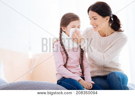 Smiling mother. Happy smiling caring mother holding a napkin near the running nose of her dear daughter