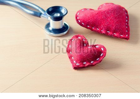 Fabric red heart and stethoscope on wooden table - state on mind mood or health condition concept tint image