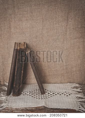 Vintage Old Book And Lace Fabric On Burlap Fabric Background