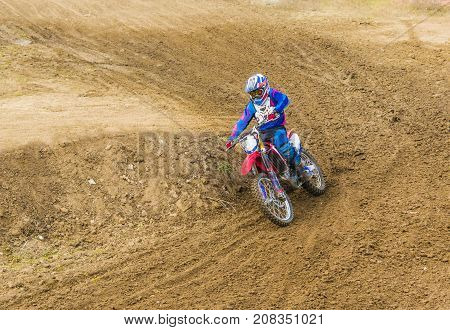 The Racer On A Motorcycle Participates In Race Motocrosses, Goes On Sand. Close-up.