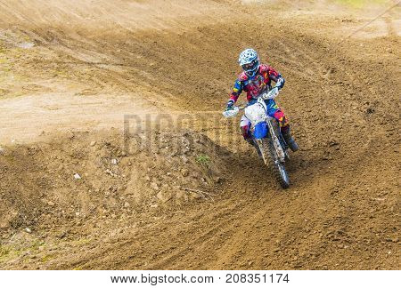 The Racer On A Motorcycle Participates In Race Motocrosses, Goes On Sand. Red Blue Suit.
