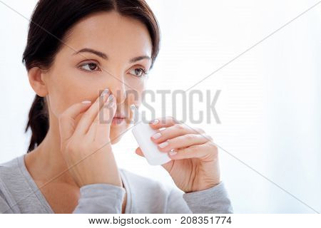 Useful drops. Allergic woman using necessary nasal drops while being at home