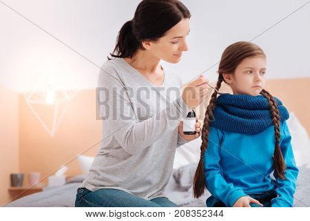 Try it. Kind cheerful smiling woman giving a spoonful of mixture to her stubborn sad ill child while sitting on the bed