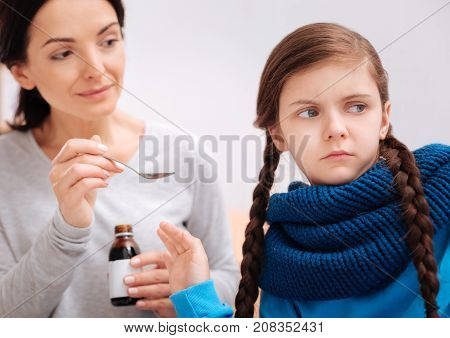 Leave me. Stubborn sad ill girl rejecting to take a spoonful of mixture from her kind smiling mother