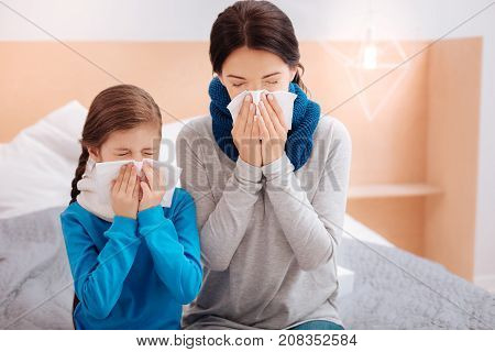 Sneezing relatives. Tired ill mother sitting with her little ill kid and sneezing