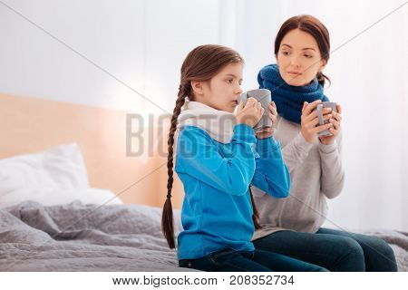 Drinking tea. Loving kind mother sitting on the bed and drinking tea together with her ill child