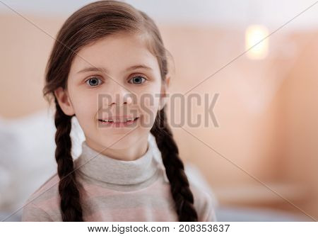 Pretty child. Adorable smiling little girl with big grey eyes being in her comfortable room
