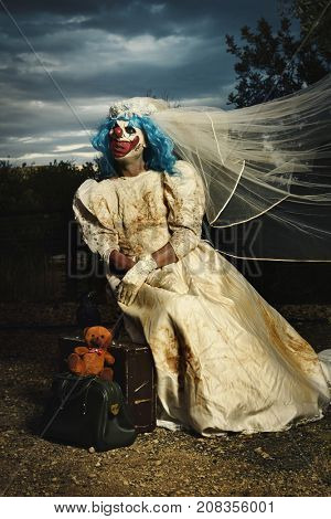a scary evil clown wearing a dirty and ragged bride dress sitting in a disturbing rural landscape at dusk, next to her luggage and a teddy bear