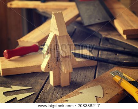 Wood working making a wooden Christmas tree decoration