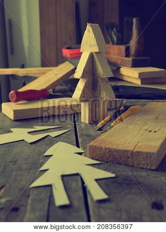 Wood working making a wooden Christmas tree decoration vintage color stylized