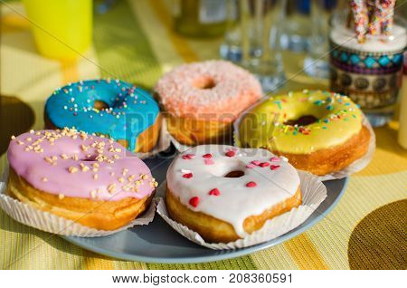 Assorted donuts in the glaze on the festive table. Sweet pastries.