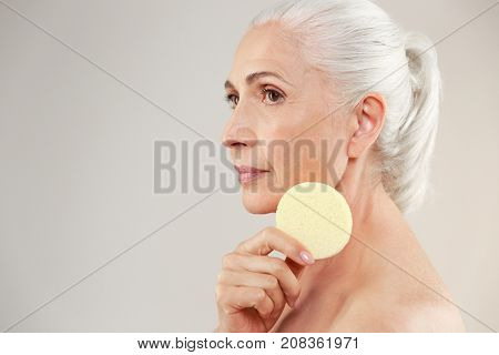 Side view beauty portrait of a lovely half naked elderly woman holding make-up sponge at her face and looking away isolated over white background