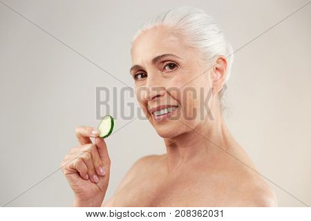 Beauty portrait of a lovely half naked elderly woman holding slice of fresh cucumber and looking at camera isolated over white background
