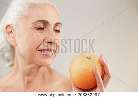 Beauty portrait of a lovely half naked elderly woman holding an orange isolated over white background