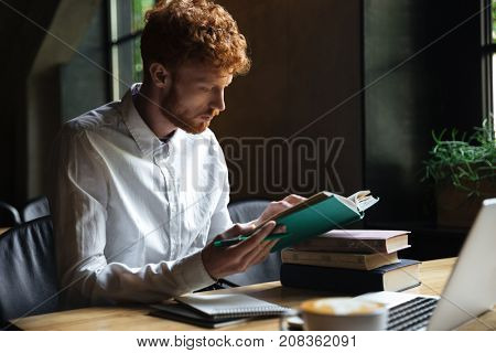 Photo of concentrated readhead bearded student, preparing for university exam in a cafe