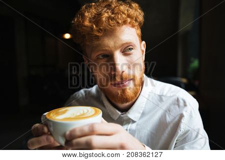 Portrait of young handsome readhead bearded man in white shirt holding coffee cup, looking aside