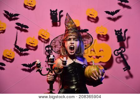 Kid In Spooky Witches Costume Holds Carved Pumpkin And Chandelier
