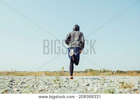 Running sport. Man runner sprinting outdoor in scenic nature. Fit muscular male athlete training trail running for marathon run. Sporty fit athletic man working out in compression clothing in sprint