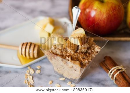 Detail of bowl of oatmeal porridge with apples cinnamon and honey on marble surface