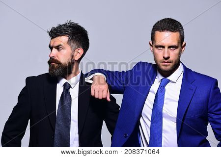 Executives present partnership friendship and strength. Business confidence and teamwork concept. Businessmen with confident faces in formal suits on grey background. Leaders rely on each other