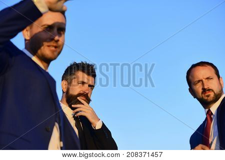 Businessmen With Serious Faces In Suits On Blue Sky Background.