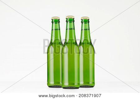 Group green longneck beer bottles 330ml mock up. Template for advertising design branding identity on white wood table.