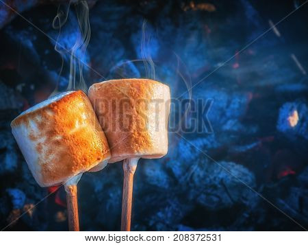 Two brown sweet marshmallows roasting over fire flames. Marshmallow on skewers roasted on charcoals.