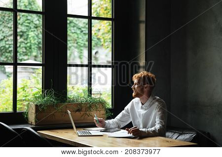 Young attractive smiling readhead bearded business man looking at window while sitting at workplace