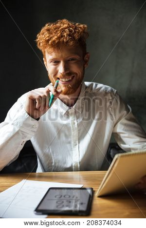 Close-up portrait of young happy readhead curly man, sitting at wooden table, holding green pan, looking at camera