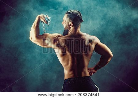 The back view of torso of attractive tattoed bearded male body builder showing his biceps with chain on dark background with smoke.