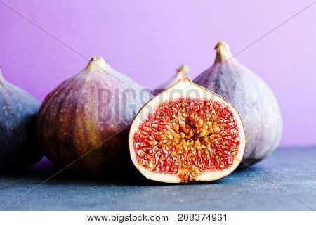 Colorfull still life organic ripe figs on stony table, beautiful purple violet background. Selective focus on sliced fruit Ficus carica