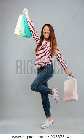 Full length image of happy asian woman in sweater rejoice with packages and looking at the camera over gray background