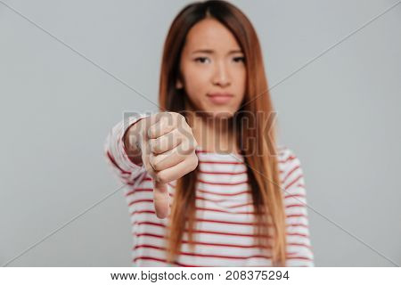 Portrait of an upset asian woman showing thumbs down and looking at camera isolated over gray background
