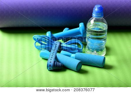 Skipping Rope, Water Bottle And Dumbbells Tied With Measuring Tape