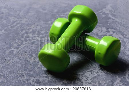 Dumbbells Made Of Bright Green Plastic On Grey Texture Background