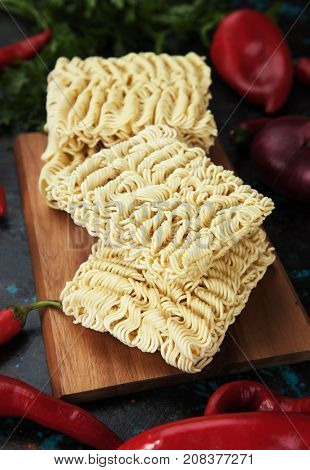 Raw asian instant noodle on wooden board