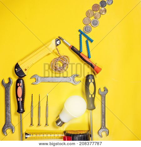 Home improvement concept. Set work hand tool for construction or repair of house. Rebuilding DIY. Group of tools in shape house. Idea conservation of energy. Concept economy of money, municipal payment.