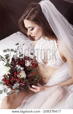 View From Above Beautiful Woman In Bridal Underwear. Girl Sitting In Bed, Holding Flowers And Waitin
