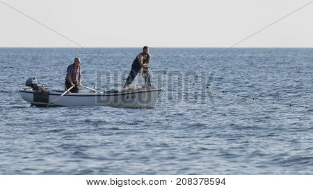 Ulcinj riviera - October 1 2017: Two fishermen fishing nets with boats in the sea on the Great Montenegrin beach Ulcinj Riviera Montenegro