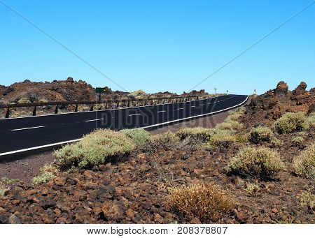 empty two lane blacktop road in the desert with scrub plants arid landscape and blue sky