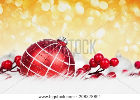 Red christmas ball on golden glitter background. Xmas card