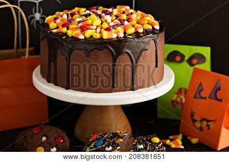 Halloween chocolate cake with candy corn and sprinkles on top and other holiday treats