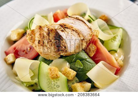Menu a gastronomic restaurant. Caesar salad with chicken with fresh vegetables on white plate on blue rustic table