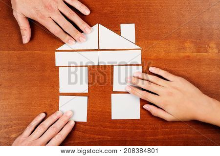 family of three joining paper pieces and forming a house