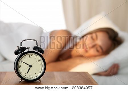 Beautiful young woman sleeping and smiling while lying in bed comfortably and blissfully on the background of alarm clock is going to ring. Sunbeam dawn on her face poster