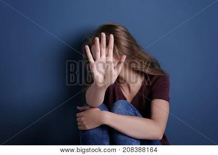 Battered sad woman sitting alone near blue wall